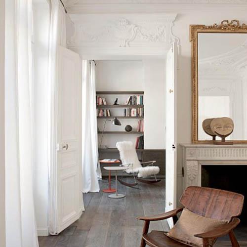 Szlachetne białe wnętrze ze sztukaterią i drewnianymi dodatkami
